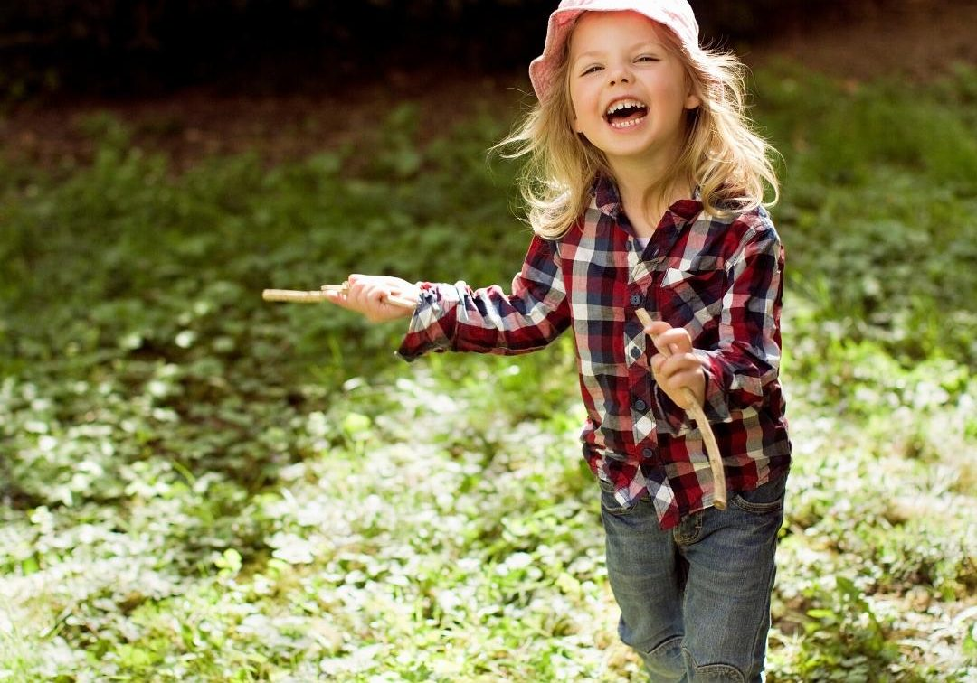 Young girl holds two sticks while smiling